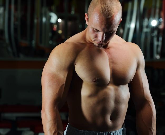 Atletische bodybuilder, uitvoeren oefening in sport sportschool hal