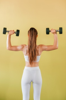 Atletische bodybuildervrouw met domoren. donkerbruin meisje in witte legging die gewichten op gele muur opheft