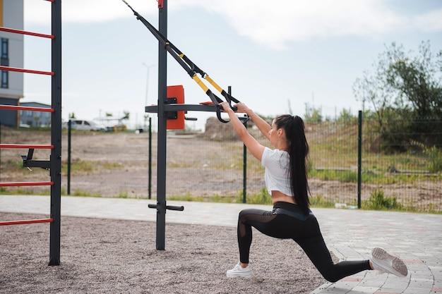 Atletische brunette vrouw in een wit t-shirt overdag traint met behulp van fitnessriemen op de speelplaats