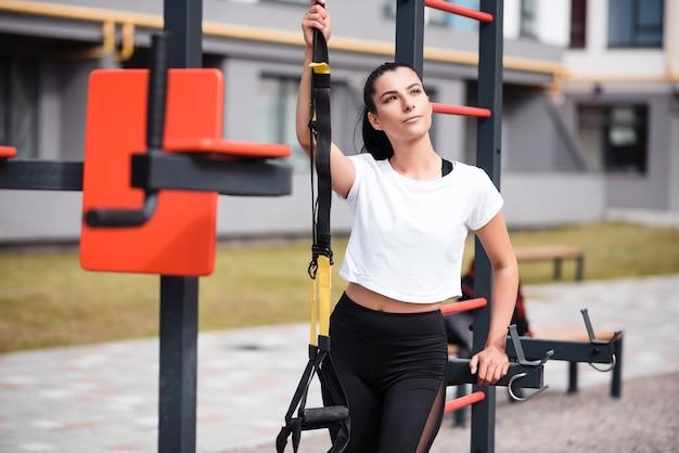 Atletische brunette vrouw in een witte t-shirt die op de speelplaats staat en fitnessriemen vasthoudt. outdoor training, portret van mooie sportieve brunette.