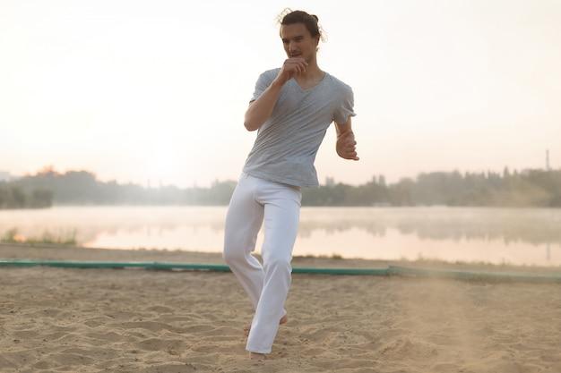 Atletische capoeiraartiest die bewegingen op het strand maakt