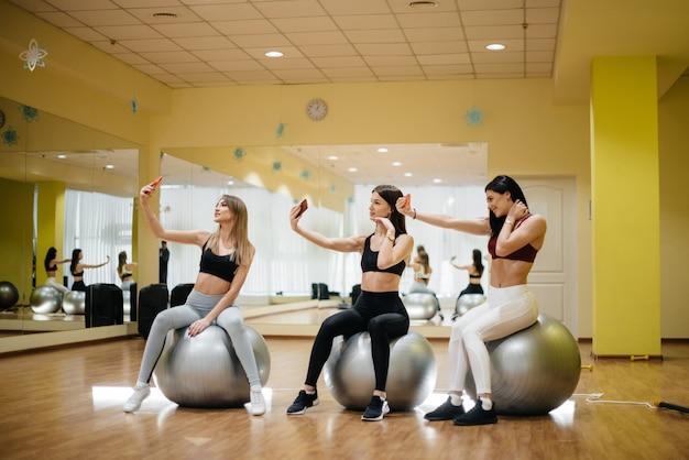 Atletische en sexy meisjes poseren voor selfies na groepsfitnesslessen. gezonde levensstijl.