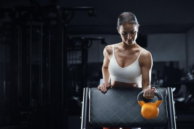 Atletische fitness vrouw bij training in sportschool spieren oppompen met kettlebell. fitness en sport concept achtergrond