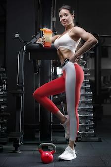 Atletische fitness vrouw bij training in sportschool spieren oppompen met kettlebell. fitness- en sportconcept
