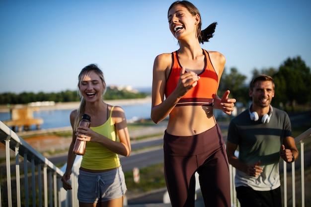 Atletische fitte mensen die samen buiten sporten en joggen. sport, vrienden, gezondheidsconcept