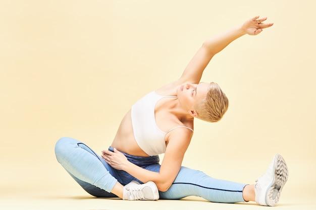 Atletische flexibele jonge vrouw in stijlvolle sportkleding doet yoga in zittende positie, zijwaarts buigen, ribben uitbreiden, één hand omhoog reiken. jongensachtig meisje beoefenen van pilates, zittend op de vloer, stretching