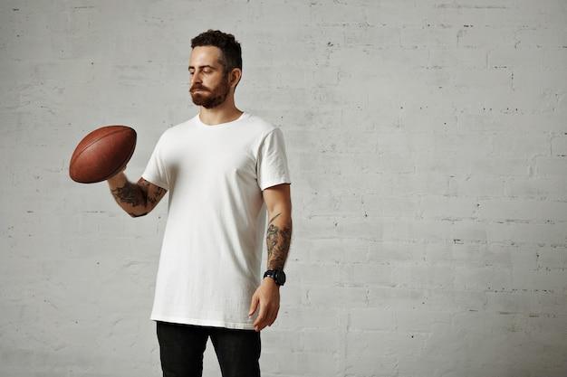 Atletische getatoeëerde hipster draagt een wit katoenen t-shirt zonder label, een zwarte spijkerbroek en een groot zwart horloge met een bruine oude rugbybal