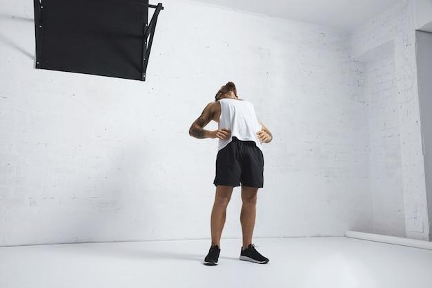 Atletische getatoeëerde man in witte lege tank t-shirt zijn borst en buikspieren strekken na training, geïsoleerd op bakstenen muur, naast zwarte trekbeugel