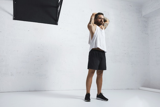 Atletische getatoeëerde man in witte lege tank t-shirt zijn triceps op armen uitrekken na training, geïsoleerd op bakstenen muur