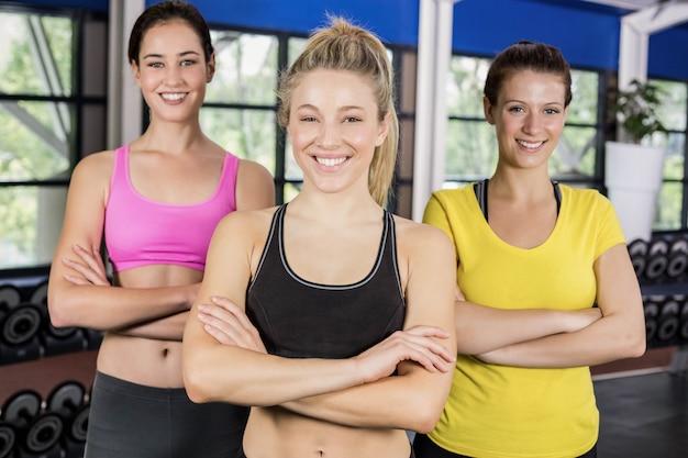 Atletische glimlachende vrouwen die met wapens stellen die in crossfitgymnastiek worden gekruist