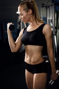 Atletische jonge dame training met gewichten