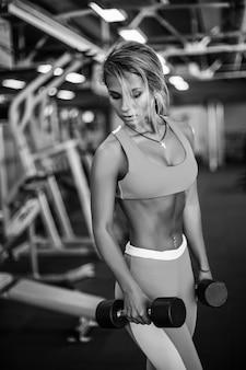 Atletische jonge geschiktheidsvrouw die in gymnastiek uitoefenen