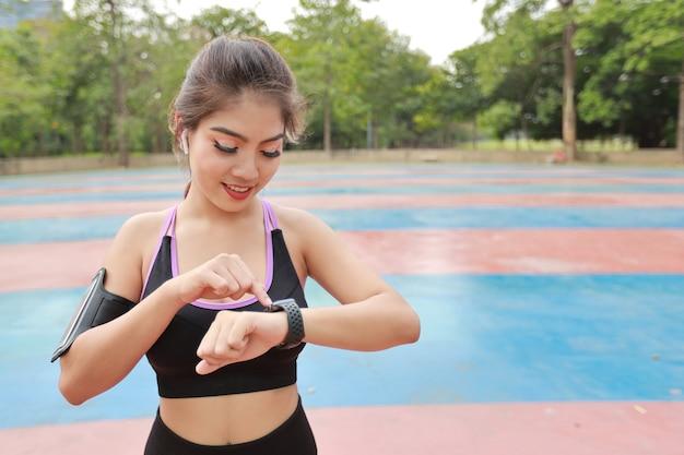 Atletische jonge gezonde aziatische vrouw in sportkleding die staat en fitnesstracker gebruikt op een slim horloge na het uitrekken buiten voor ochtendoefening. sport- en technologieconcept