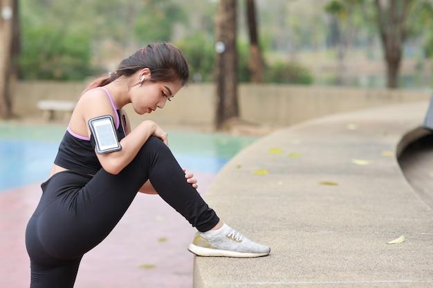 Atletische jonge gezonde en schoonheids aziatische vrouw in sportkleding die buiten staat en zich uitstrekt voor ochtendoefening. actief meisje trainen op biceps oefenen met mobiele telefoon. sport en lifestyle concept
