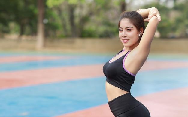 Atletische jonge gezonde en schoonheids aziatische vrouw in sportkleding die buiten staat en zich uitstrekt voor ochtendoefening. actief meisje trainen op biceps-oefening. sport en lifestyle concept