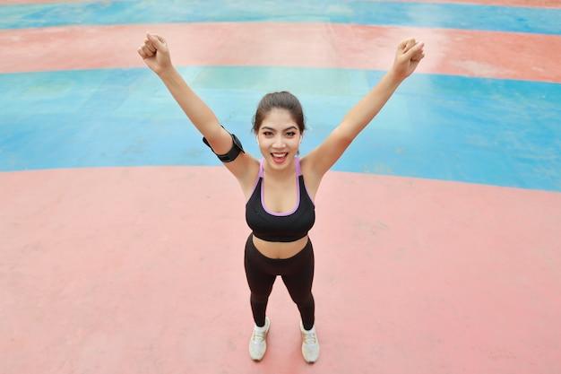 Atletische jonge gezonde en schoonheids aziatische vrouw in sportkleding die staat en handen buiten opsteekt voor ochtendoefening. actief meisje trainen op biceps stretching oefening. sport en lifestyle concept