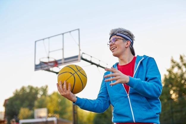 Atletische jonge jongen in vrijetijdskleding die dol is op basketbal, geniet van buiten spelen