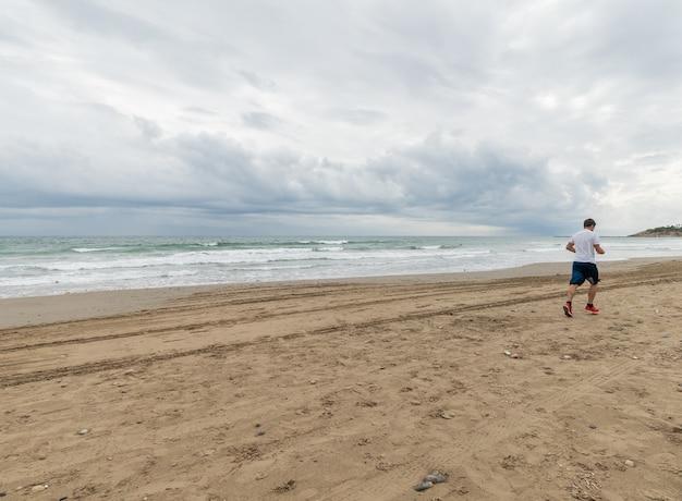 Atletische jonge kerel die het zand op het strand doorneemt