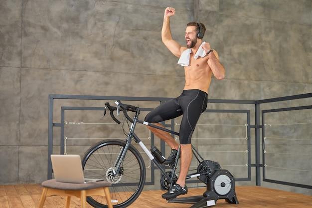 Atletische jonge man die hand opsteekt en schreeuwt van vreugde tijdens het fietsen op de hometrainer