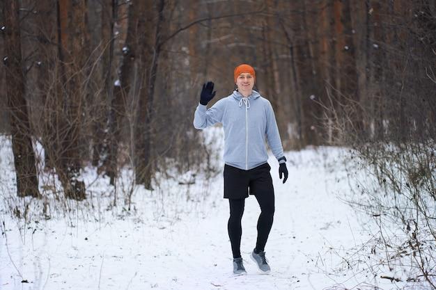 Atletische jonge man die in de winterbos loopt, dat een groetengebaar toont