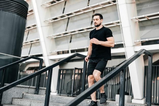 Atletische jonge man loopt van de trap af. stedelijk sportconcept. flatgebouw op achtergrond. actief leven. buiten fitnessen. man in zwarte sportkleding joggen in de ochtend.