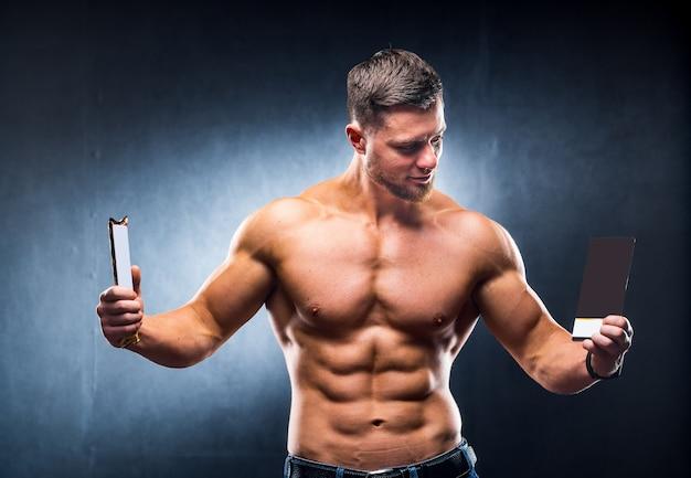 Atletische jonge man met sportreep en chocolade. kiezen tussen gezond en schadelijk voedsel. naakte torso. grijze achtergrond. horizontale foto. detailopname