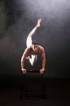 Atletische jonge mens die en op houten tribune springen leunen terwijl het bekijken camera