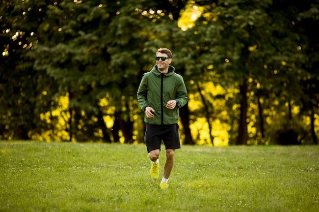 Atletische jonge mens die terwijl het doen van training in zonnig groen park loopt