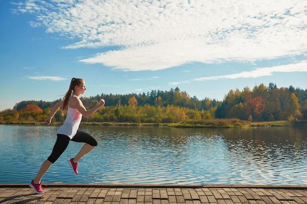 Atletische jonge roodharige witte lachende vrouw in roze sneakers joggen langs de rivier aan de rivier. zonnig wormweer in de herfst.