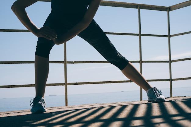 Atletische jonge vrouw die ochtendoefeningen op de achtergrond van het overzees doet