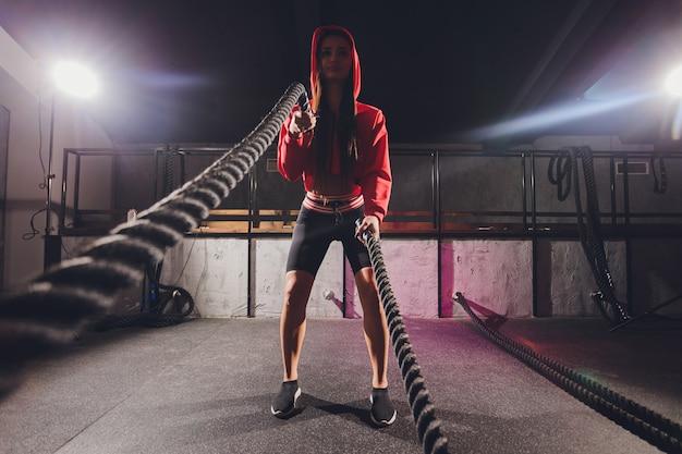 Atletische jonge vrouw die sommige oefeningen met een kabel doet openlucht.