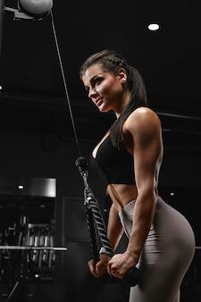 Atletische jonge vrouw die tricepsoefeningen op een terriër in de gymnastiek doet.