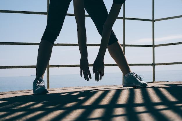 Atletische jonge vrouw die zich het uitrekken in de ochtend op de achtergrond van het overzees doet