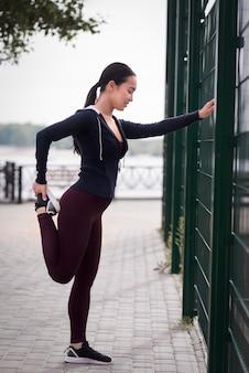 Atletische jonge vrouw die zich in openlucht uitrekt