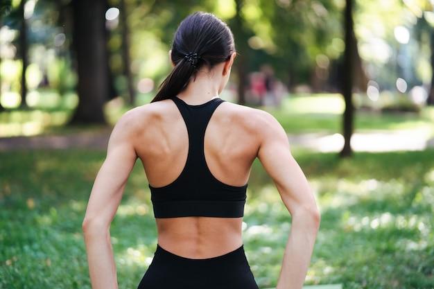 Atletische jonge vrouw doet yoga in het park in de ochtend, de opleiding van vrouwen op een yogamat