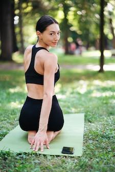 Atletische jonge vrouw doet yoga in het park in de ochtend.