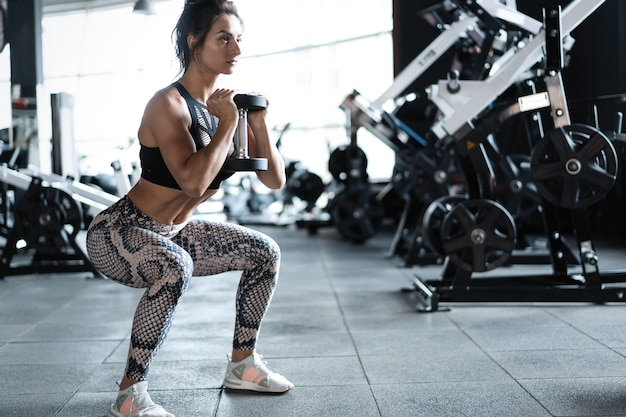 Atletische jonge vrouw fitness model squats oefening doet