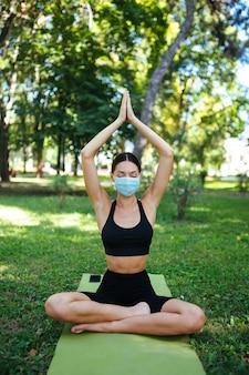 Atletische jonge vrouw in een medisch beschermend masker, doet yoga in het park in de ochtend, de opleiding van vrouwen op een yogamat