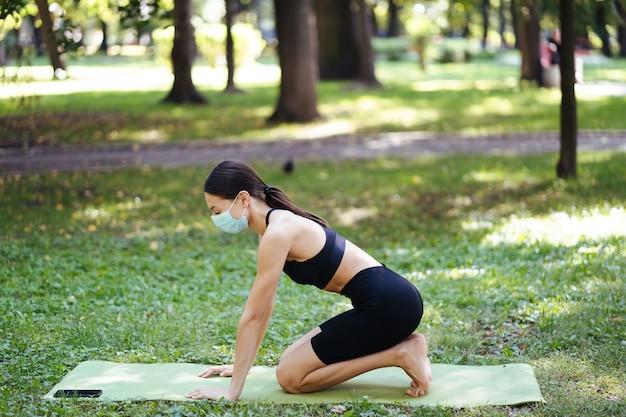 Atletische jonge vrouw in een medisch beschermend masker, doet yoga in het park in de ochtend