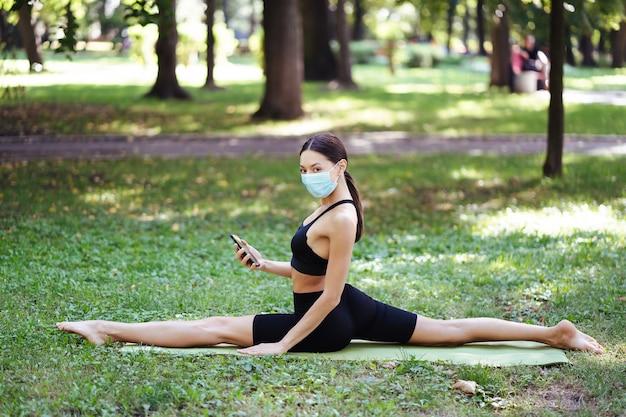 Atletische jonge vrouw in een medisch beschermend masker, yoga doet in het park