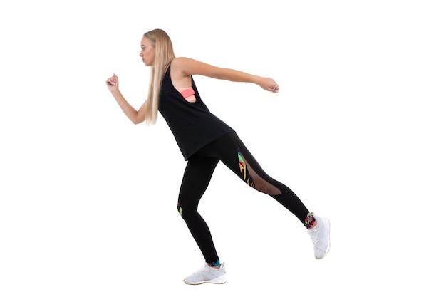 Atletische jonge vrouw in een roze top, beenkappen en sneakers squats