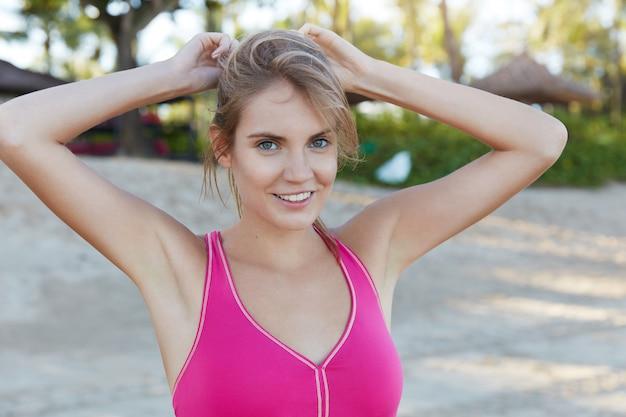 Atletische jonge vrouw in roze top, heeft een vrolijke uitdrukking voor sport buiten, warmt op aan zandstrand. fashion sportmodel recreëert na een uitgeputte training, heeft een perfecte lichaamsvorm