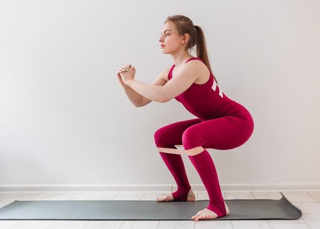 Atletische jonge vrouw maakt zijbalk. meisje warmt benen op, met behulp van fitness elastiekje. roze rubber voor thuisoefeningen. binnen en buiten trainen. sport en gezond actief levensstijlconcept.