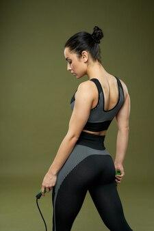 Atletische jonge vrouw met springtouw poseren in studio