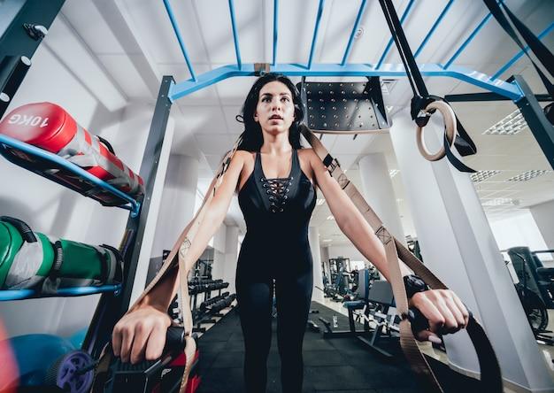 Atletische jonge vrouw training met trx fitness riemen.