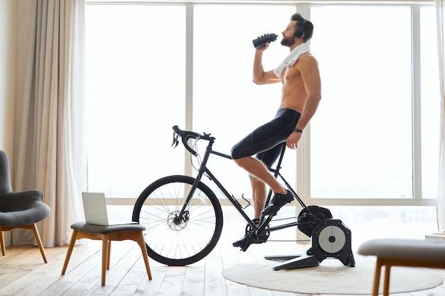 Atletische jongeman die op een briefpapierfiets rijdt en water drinkt