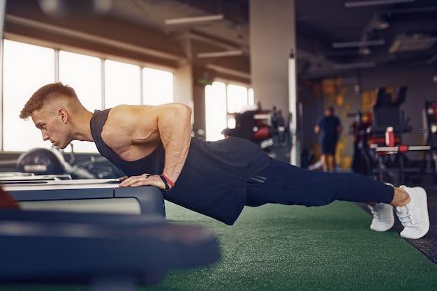 Atletische jongeman doet push-ups in de sportschool