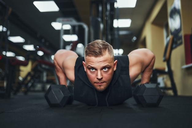 Atletische jongeman doet pushups in de sportschool gespierde en sterke man uit te oefenen