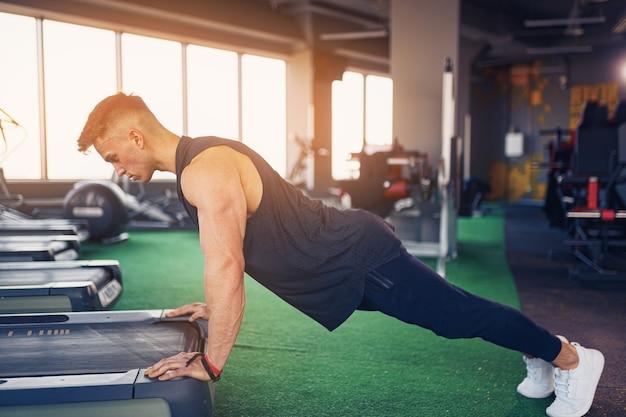 Atletische jongeman doet pushups in de sportschool