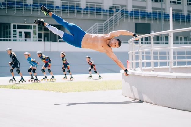 Atletische jongeman voert gymnastische elementen uit. man doet menselijke vlag oefening